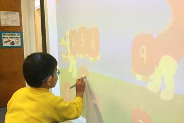 Nursery Class Chinese New Year - learnnig numbers with a Chinese Dragon on the whiteboard