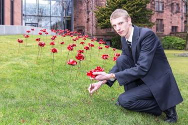 School Captain, Paul Greenhalgh, lays one of the 81 poppies in tribute to the Old Boys who lost their lives in the Great War