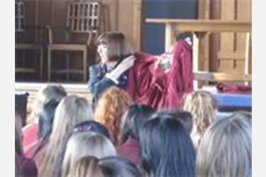 Mrs Haslam shows the girls a Prefect's gown, with the names of all its owners sewn inside
