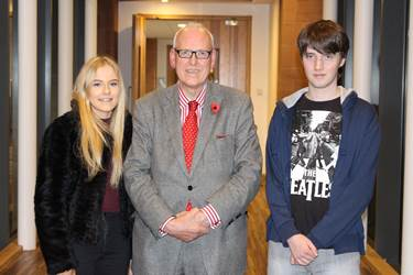 Sixth Form students Charlotte Bodger and Myles Blackwell welcome Lord Hennessy to Bolton School