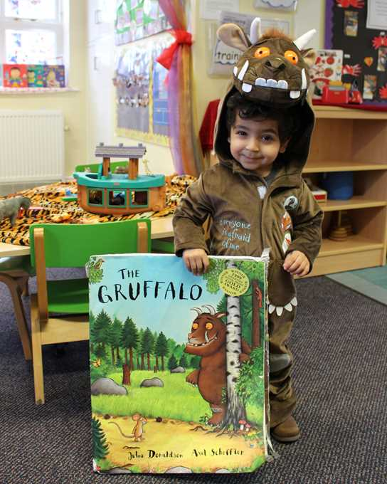 A toddler dressed in a brown Gruffalo costume with a large copy of the book 'The Gruffalo'