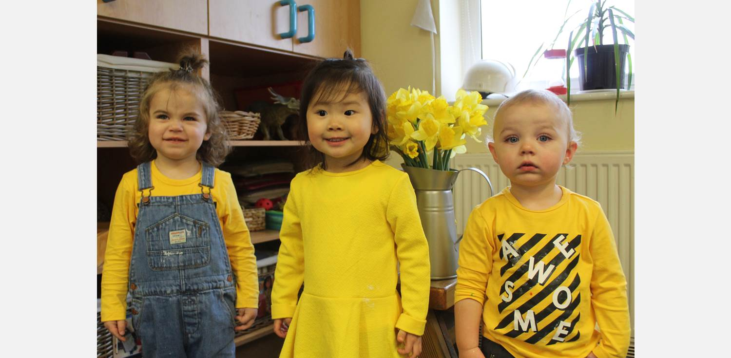 St David's Day 2019 - three toddlers wearing yellow with jug of daffodils in the background