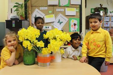 Children wearing yellow, sitting and standing around a table on which are three vases bursting with daffodils