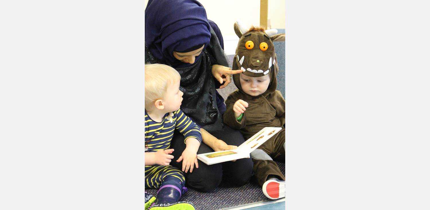 World Book Day - staff members reading a book with two babies, one wearing a Gruffalo costume