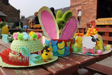 Three colourful Easter bonnets: a green straw hat on the left with multicoloured fluffy chicks and a red fence; a crown with rabbit ears and colourful butterflies and chicks stuck to the band; and a sun-hat with chicks, colourful eggs and a sheet around the brim.