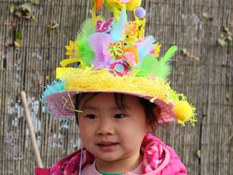 A girl wearing an elaborate Easter Bonnet: a pink straw hat with a tower of feathers, eggs and butterfly shapes on top