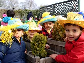 Boys wearing straw hat style Easter Bonnets while crowding around small shrubs in plant pots