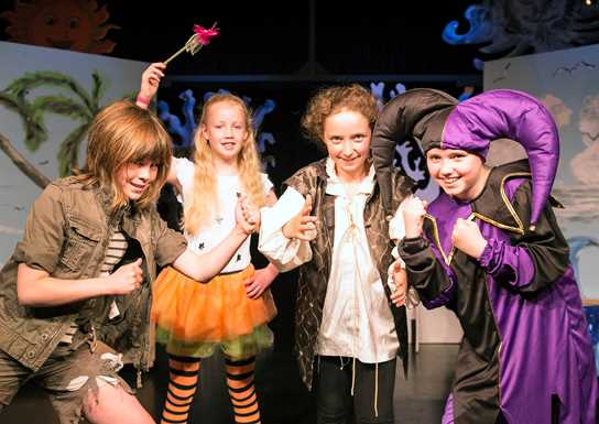 A group of 4 girls in elaborate costumes acting for the camera. They are on a stage. A jester in a tunic that is half purple and half black with a 'starburst' collar, wearing a double-pointed jester's cap with bells, has her fists up ready to box against another girl in tattered brown clothing. A fairy wearing a bright orange tutu, white t-shirt and black and orange striped leggings holds up her magic wand. Another girl in a white tunic and brown sleeveless coat is about to start the match.